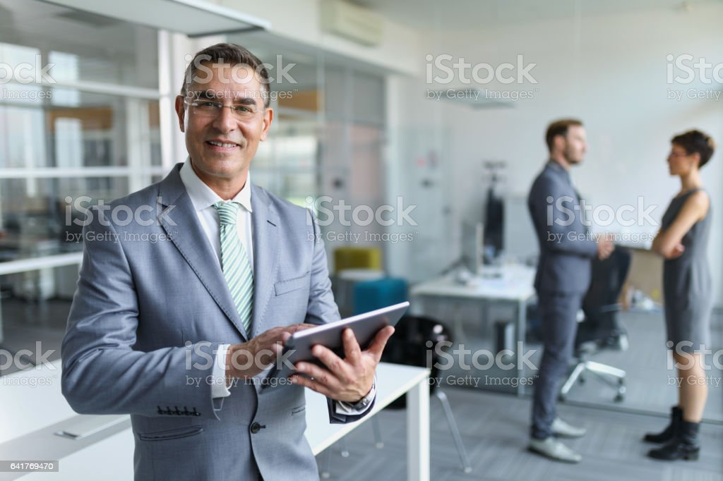 Mature businessman using digital tablet in the office stock photo