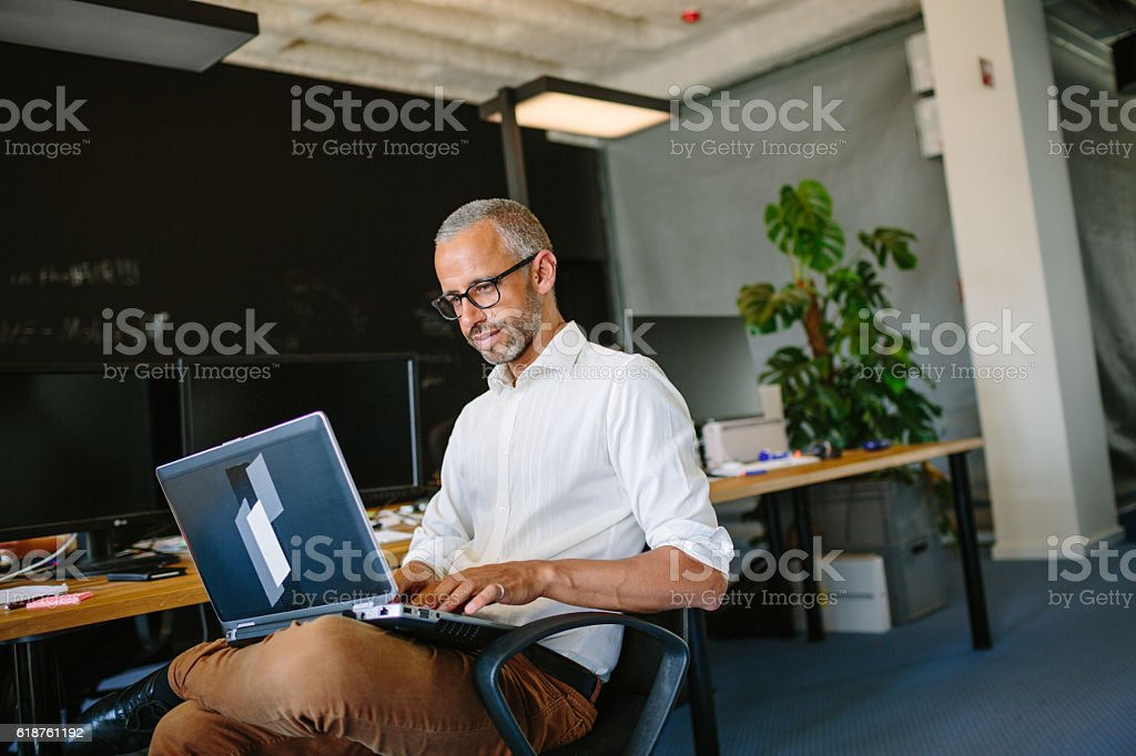 Mature businessman using laptop at startup stock photo