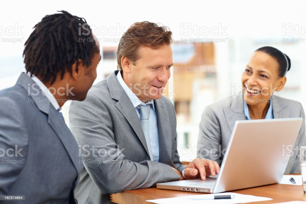 Mature businessman using laptop with his colleagues in office royalty-free stock photo
