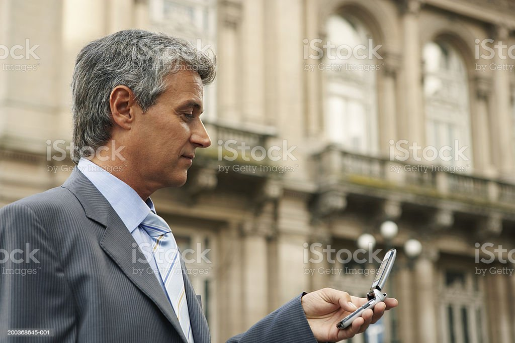 Mature businessman using mobile phone, close up, side view royalty-free stock photo