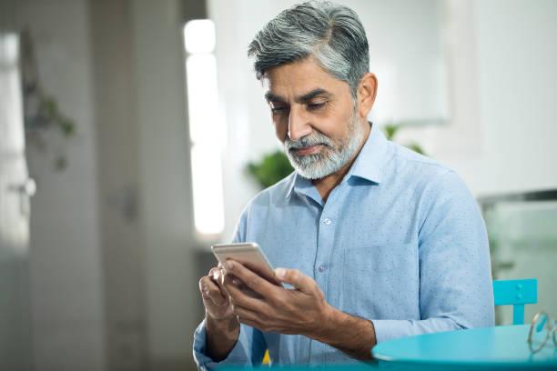 Mature businessman using mobile phone stock photo