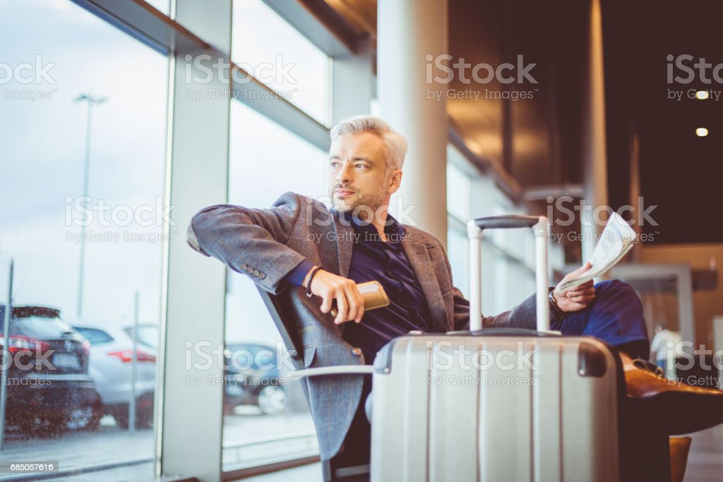 Mature businessman waiting at airport lounge stock photo