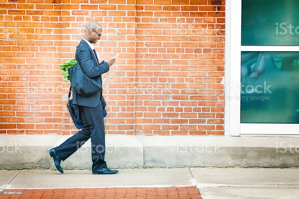 Mature businessman walking back home with groceries stock photo