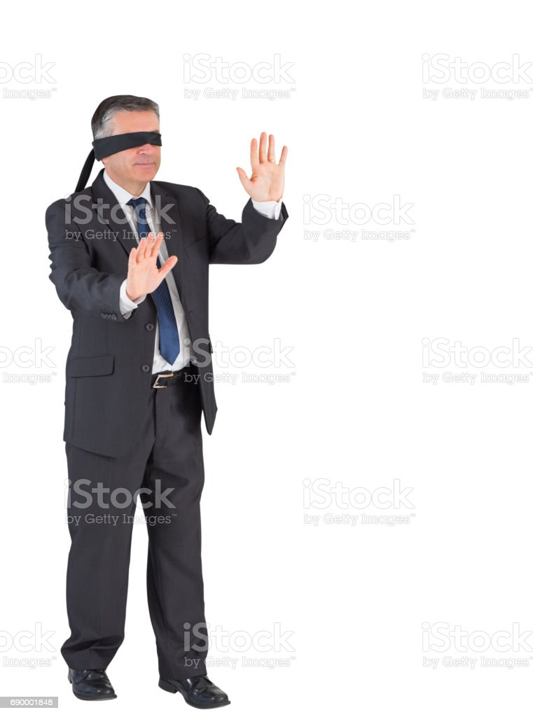 Mature businessman walking with blindfold stock photo