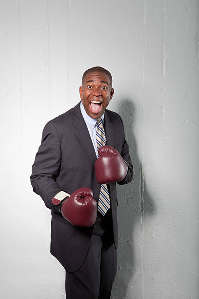 Mature businessman wearing boxing gloves, smiling stock photo