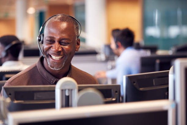 Mature Businessman Wearing Telephone Headset Talking To Caller In Customer Services Department Mature Businessman Wearing Telephone Headset Talking To Caller In Customer Services Department call centre photos stock pictures, royalty-free photos & images