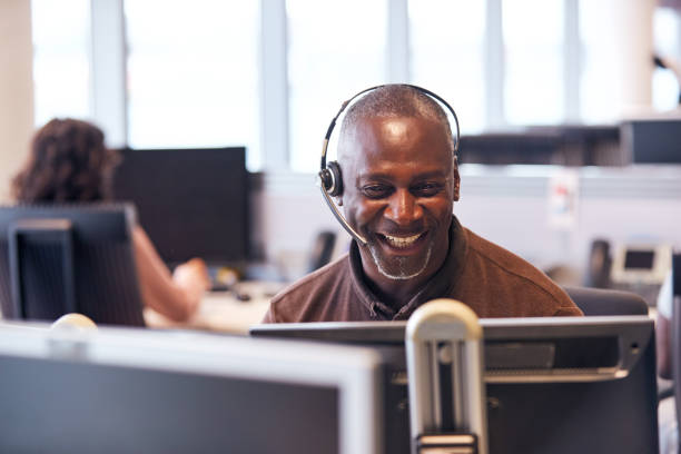 Mature Businessman Wearing Telephone Headset Talking To Caller In Customer Services Department stock photo
