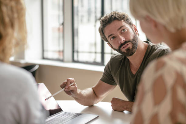 Mature businessman with beard pointing at laptop with pencil and listening to colleague stock photo