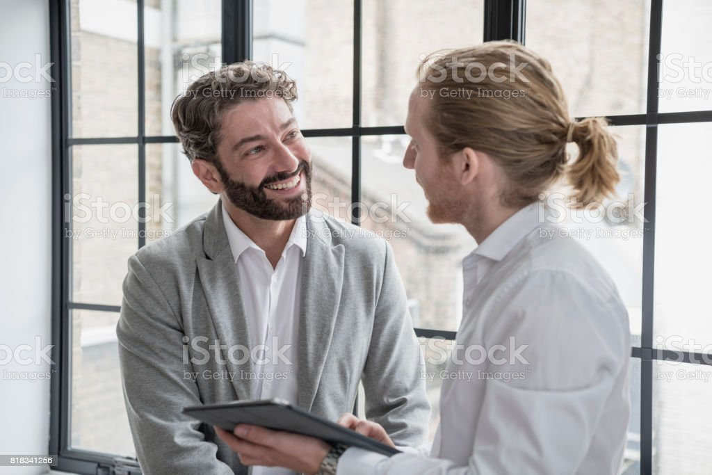 Mature businessman with beard smiling and listening to young male colleague with tablet stock photo