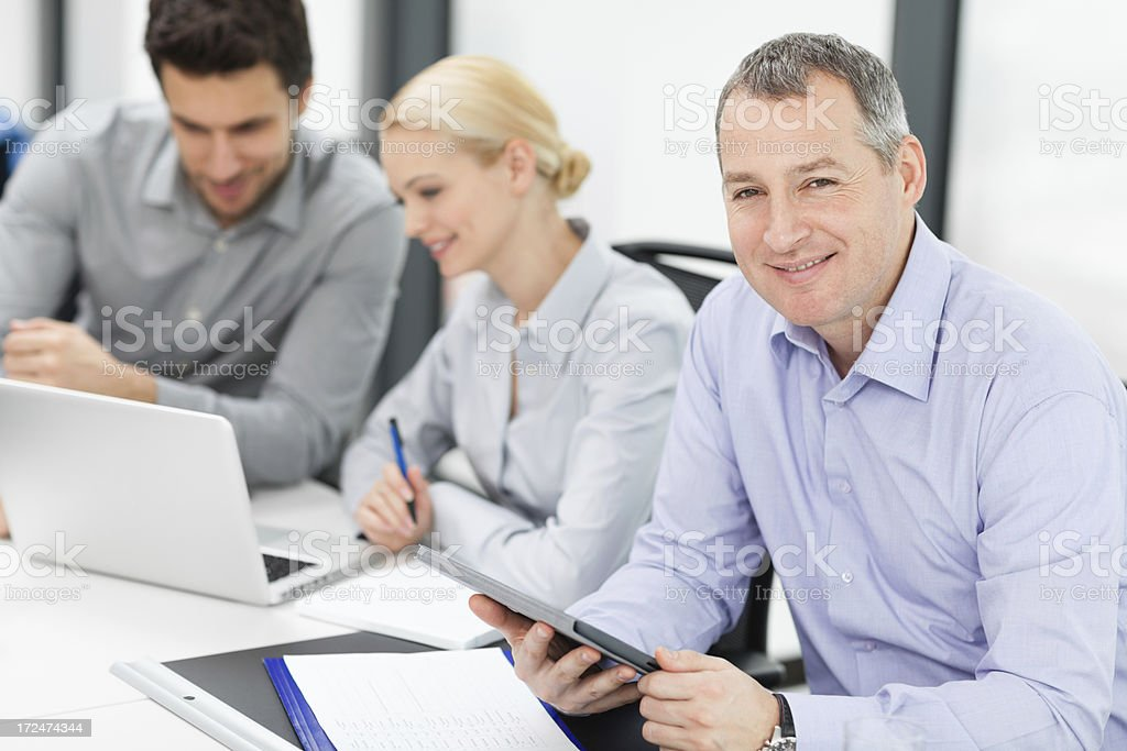 Mature businessman with colleagues in backgroung royalty-free stock photo