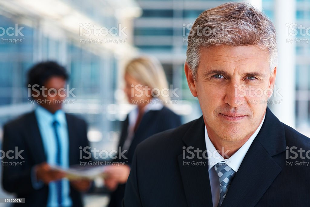 Mature businessman with colleagues in the background stock photo