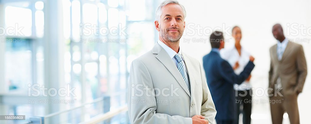 Mature businessman with colleagues in the background royalty-free stock photo
