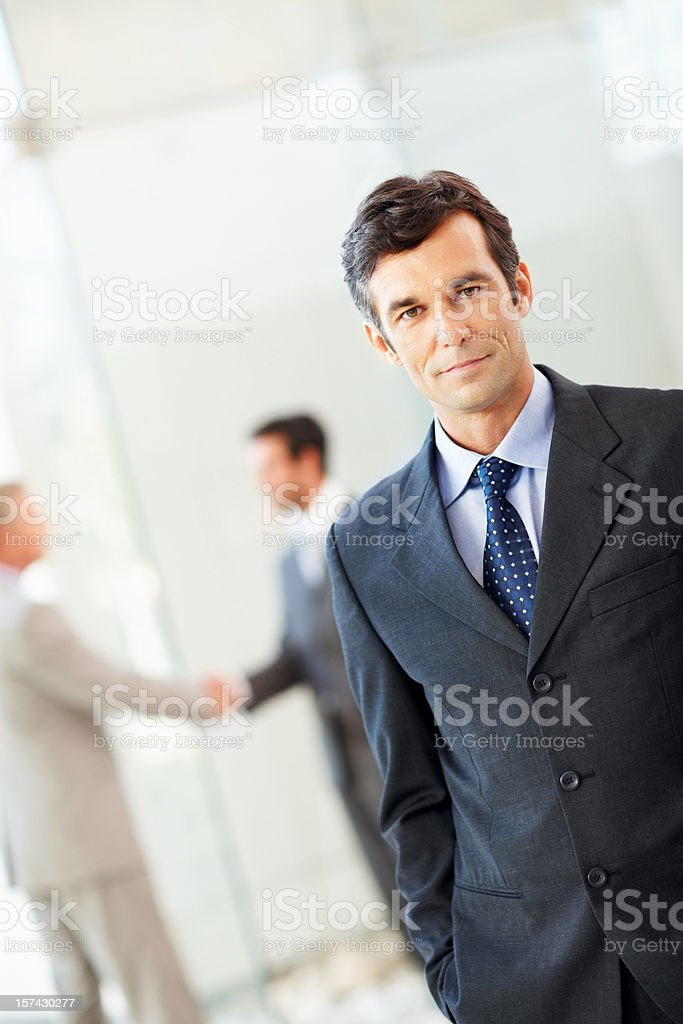Mature businessman with his hands in pockets royalty-free stock photo