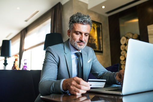 istock Mature businessman with laptop in a hotel lounge. 912065676