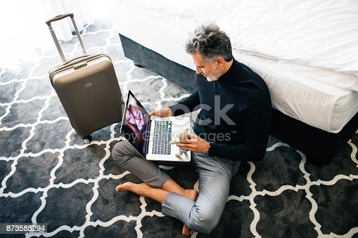 istock Mature businessman with laptop in a hotel room. 873585294