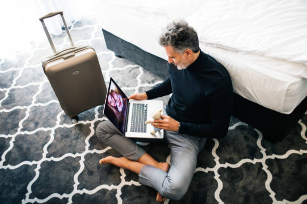 Mature businessman with laptop in a hotel room. stock photo