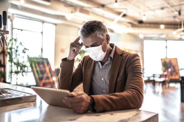 Mature businessman with mask using digital tablet at work stock photo