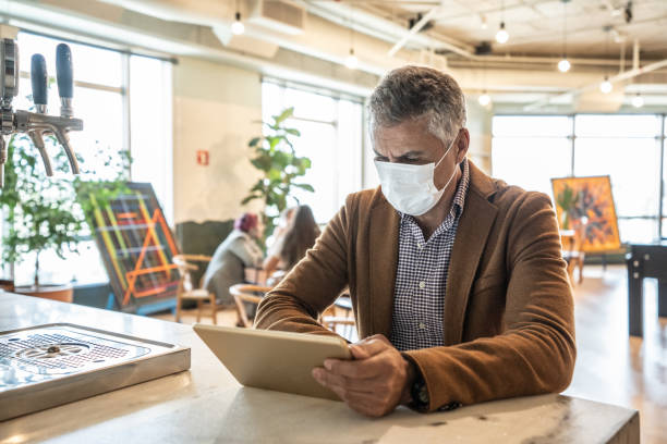 mature businessman with mask using digital tablet at work - businessman covid mask foto e immagini stock