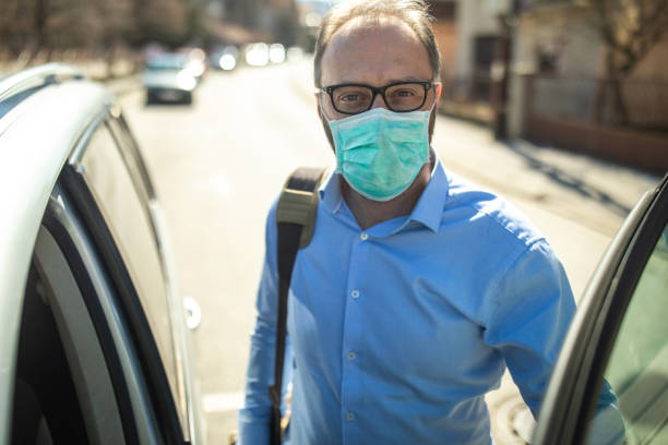 Reifer Geschäftsmann mit Schutzmaske ins Auto – Foto