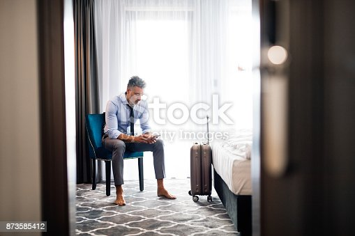 istock Mature businessman with smartphone in a hotel room. 873585412