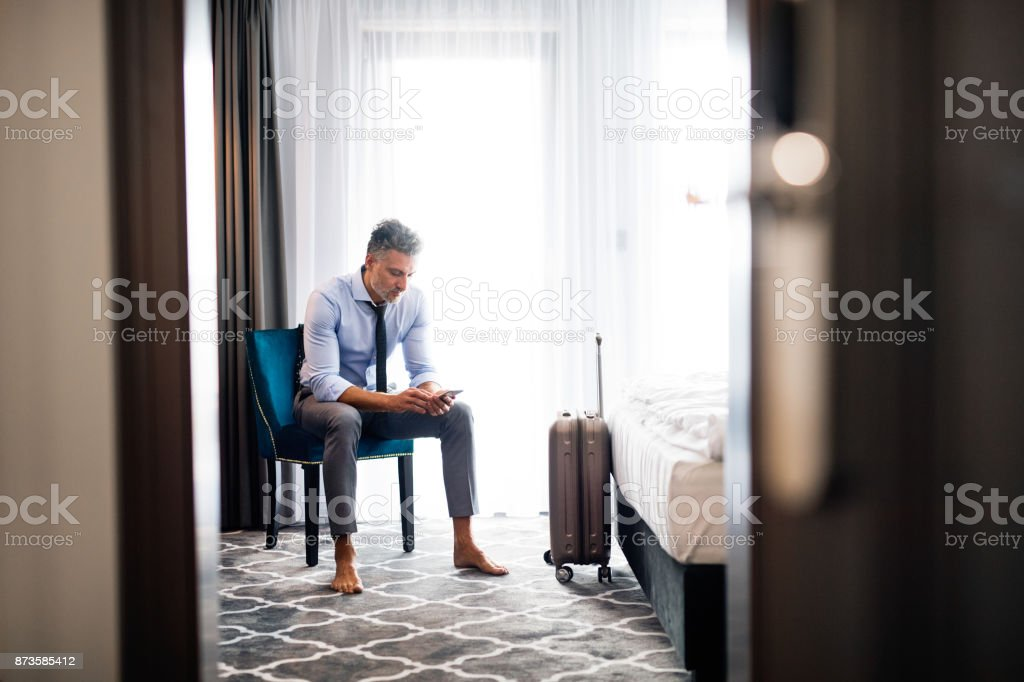 Mature businessman with smartphone in a hotel room. stock photo