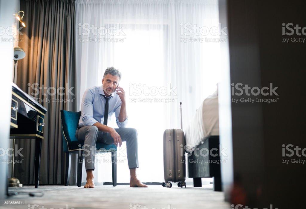 Reife Geschäftsmann mit Smartphone in einem Hotelzimmer. – Foto