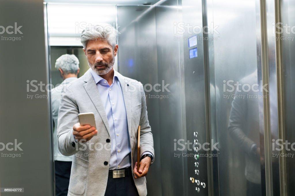 Reife Geschäftsmann mit Smartphone in den Aufzug. – Foto