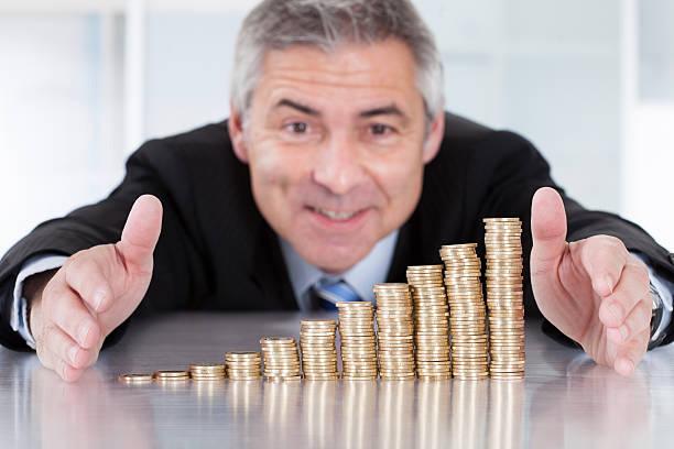 mature businessman with stack of coins - hair grow cyclus stockfoto's en -beelden