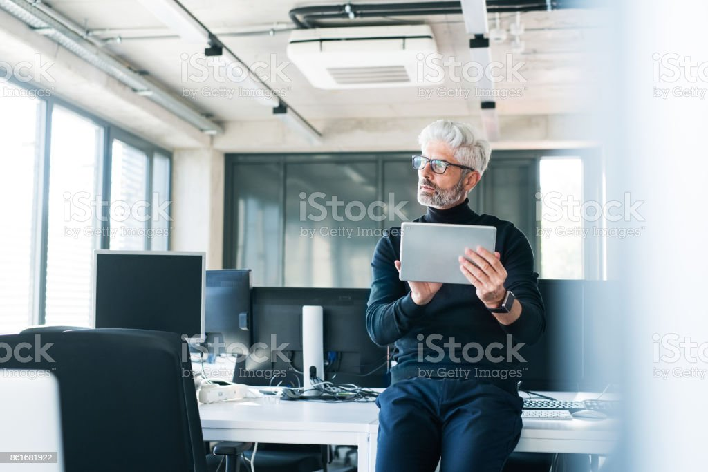 Mature businessman with tablet in the office. stock photo