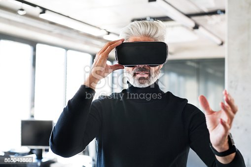 istock Mature businessman with VD goggles in the office. 865043866