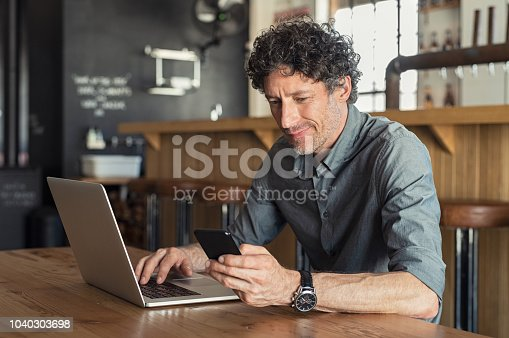 Happy mature business man sitting at cafeteria with laptop and smartphone. Businessman texting on smart phone while sitting in a pub restaurant. Portrait of senior formal man working and checking email on computer.