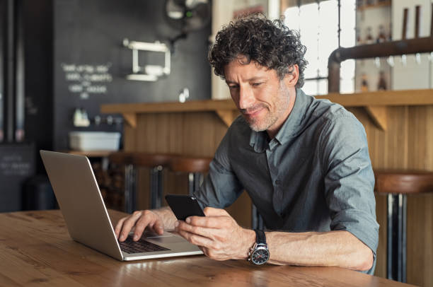 mature businessman working at cafe - owner laptop smartphone foto e immagini stock