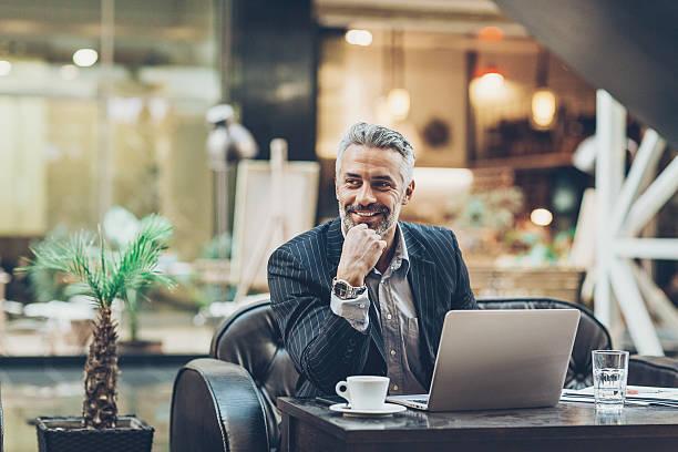mature businessman working in comfort - amministratore delegato foto e immagini stock