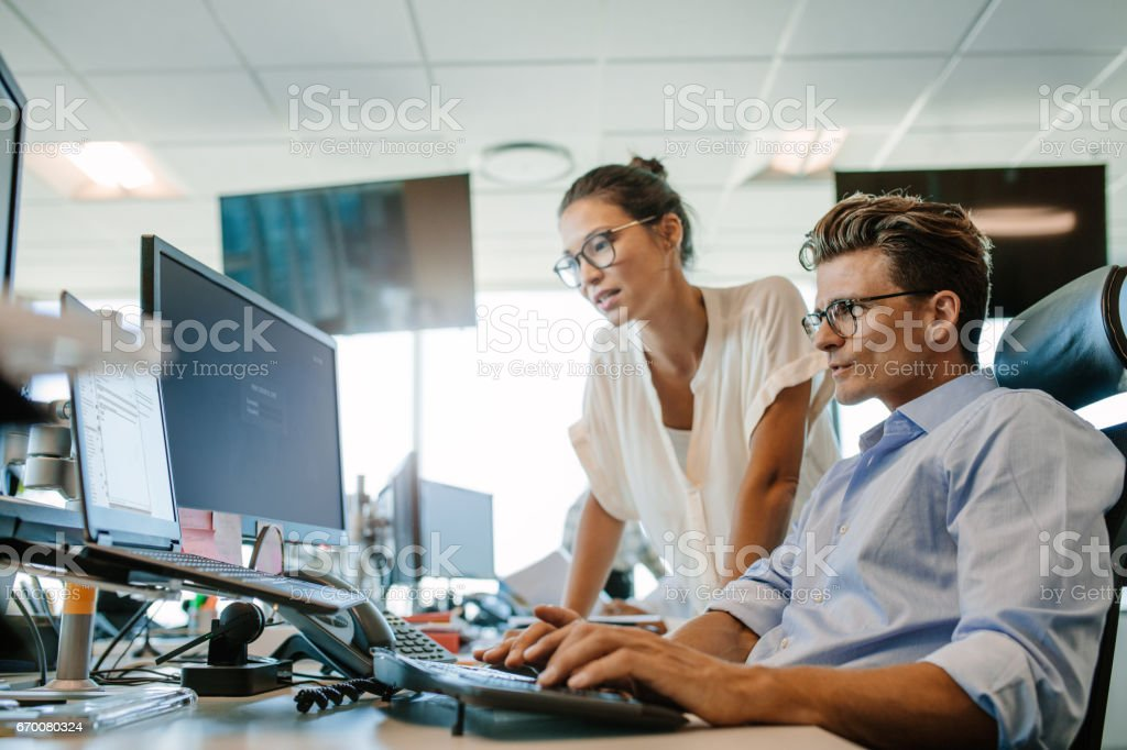 Mature businessman working on computer with colleague stock photo