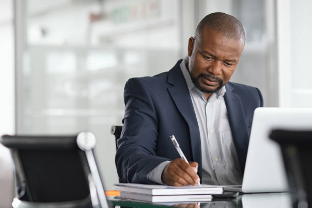 Mature businessman writing on documents African serious businessman writing notes and using laptop. Mature business man writing his strategy on notebook while using laptop in modern office. Focused black entrepreneur sitting at desk in modern office while working. black ethnicity stock pictures, royalty-free photos & images