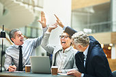 Mature businesspeople excitedly high fiving together in an office