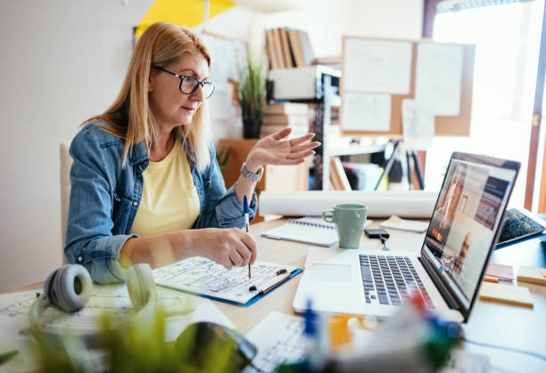Mature businesswoman attending web conference and communicates with colleagues remotely stock photo