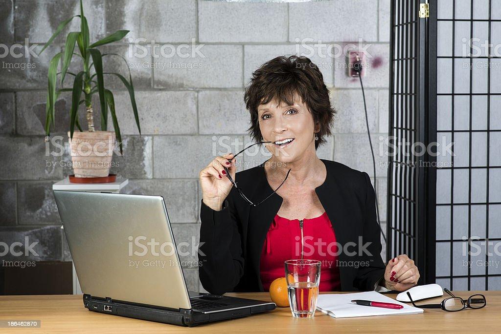 Mature businesswoman biting on glasses royalty-free stock photo