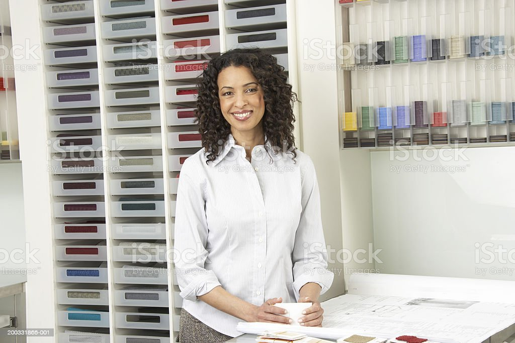 Mature businesswoman by colour samples in shop, smiling, portrait royalty-free stock photo