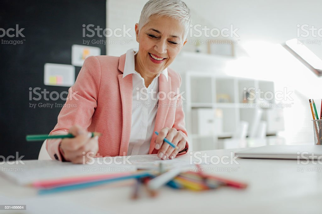 Mature Businesswoman Coloring Book In Her Office. stock photo