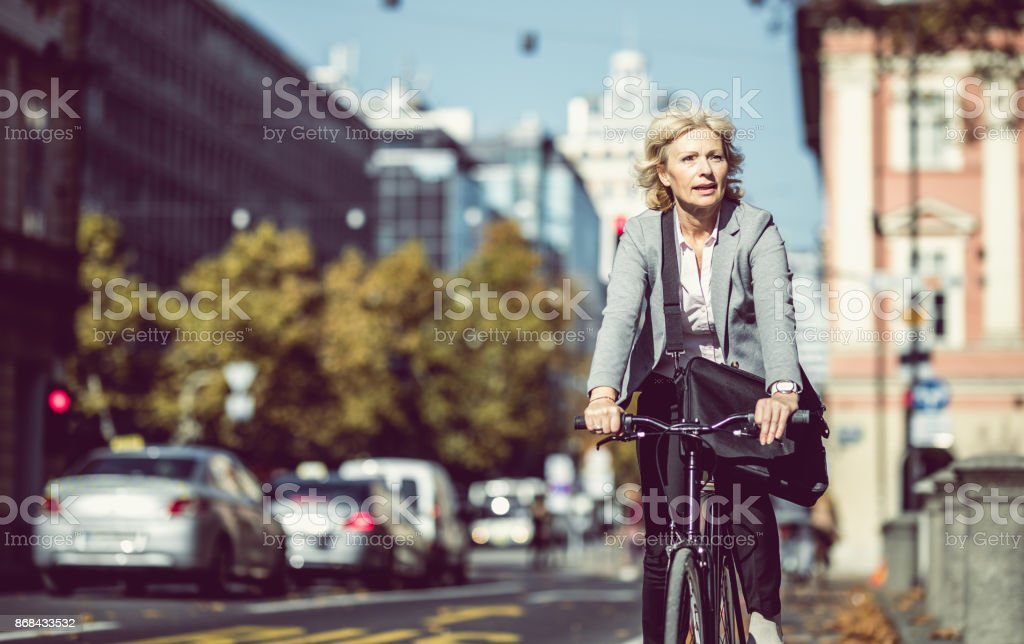 Mature Businesswoman Commuting on Bicycle stock photo