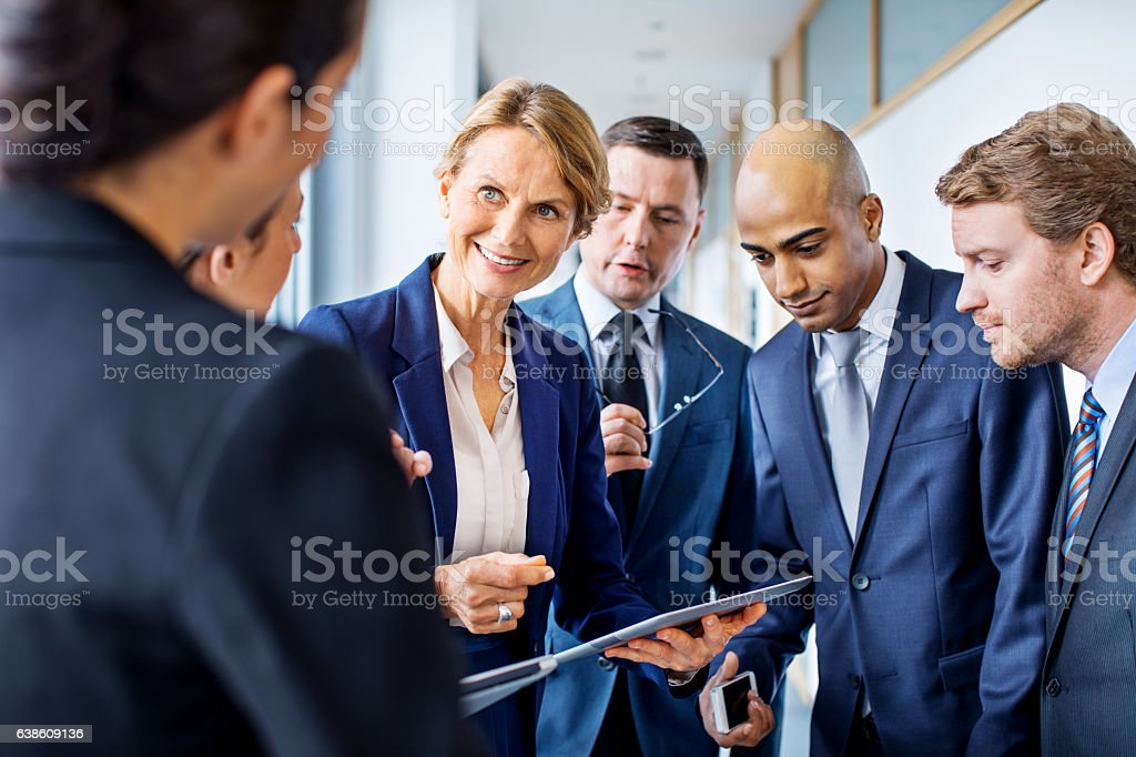Mature businesswoman discussing work with colleagues in office hallway stock photo