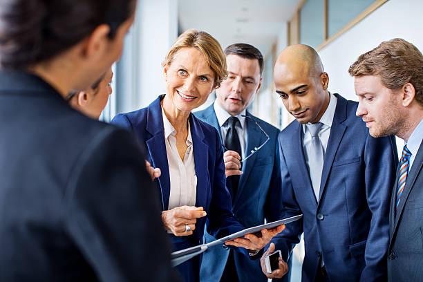 mature businesswoman discussing work with colleagues in office hallway - alvarez stock-fotos und bilder