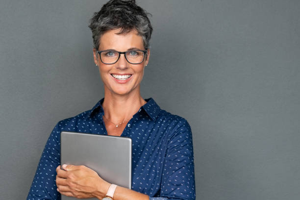 mature businesswoman holding digital tablet - senior business woman tablet imagens e fotografias de stock