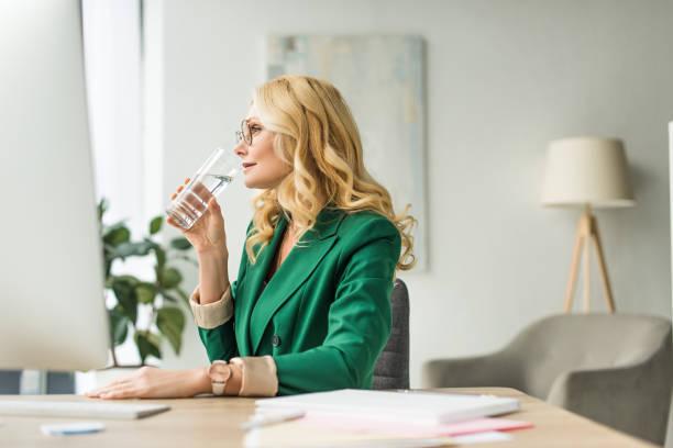 reife geschäftsfrau im brillen-trinkwasser - leitungswasser trinken stock-fotos und bilder