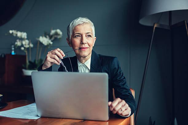 mature femme d'affaires dans son bureau. - directrice photos et images de collection