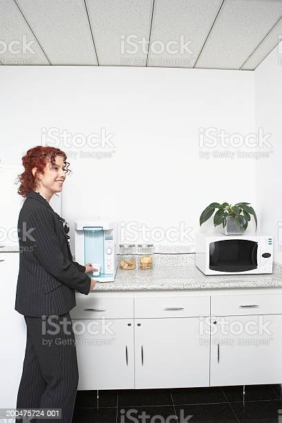Mature Businesswoman In Office Kitchen Side View Stock Photo - Download Image Now