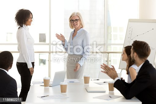 509032417 istock photo Mature businesswoman introducing new worker to colleagues 1155902211