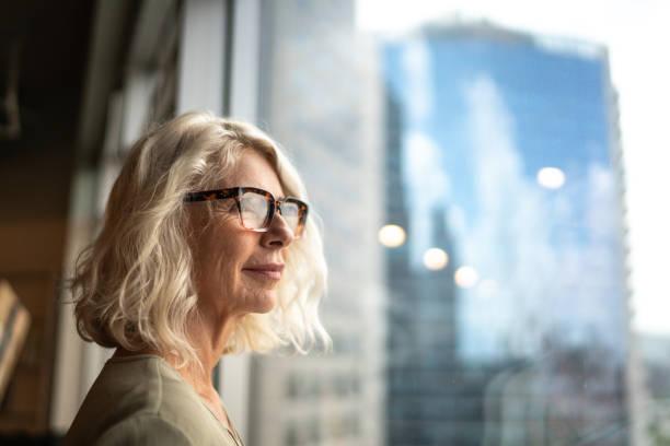 dojrzała bizneswoman patrząc przez okno - nadzieja zdjęcia i obrazy z banku zdjęć