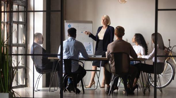 mature businesswoman mentor coach give flip chart presentation at workshop - pensionati lavoratori foto e immagini stock